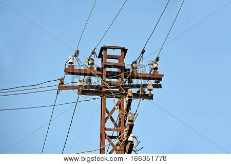 Old electric lines pylon on blue sky background