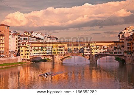Florence, Tuscany, Italy: landscape at sunset of the landmark Ponte Vecchio, the famous medieval bridge over the Arno river with old shops of artisan goldsmiths and jewelers