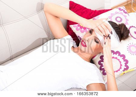 A beautiful young woman laying on the sofa with a bandage on her head.