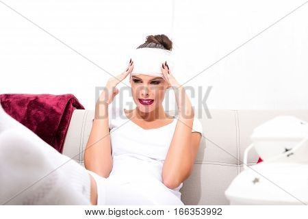 A beautiful young woman siting on the sofa with a bandage on her head.