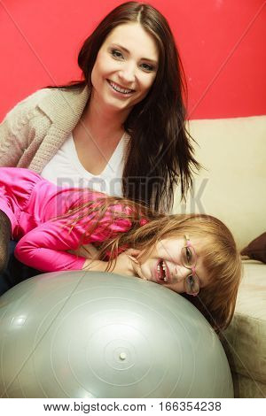 Family parenthood happiness concept. Mother sitting exercise balance ball relaxing and having fun with her daughter