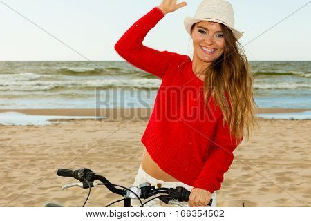 Sports and recreation. Attractive smiling woman with bicycle walks on beach near to sea. Young long haired gorgeous tourist spends time on seaside.