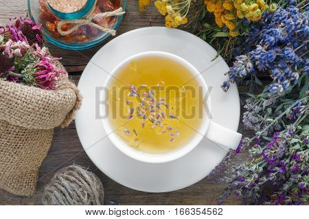 Medicinal herbs cup of healthy tea and bag of dry healthy coneflowers on wooden table. Herbal medicine. Top view flat lay.