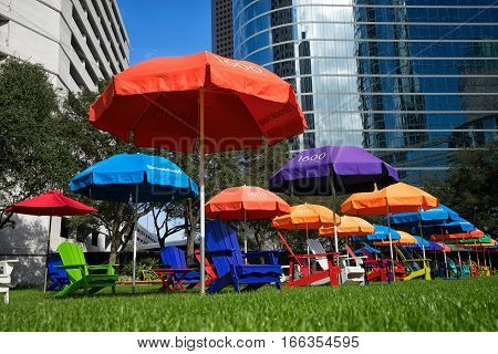 December 29, 2015 Houston Texas: colourful patio chairs on green grass in the financial district offer a resting spot for office workers