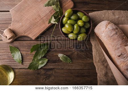 Green olives on a wooden board ciabatta bay leaf on wooden background. Ciabatta