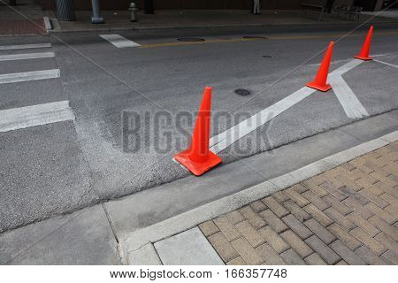 Orange roadwork cones on the asphalt road, pedestrian crossing.