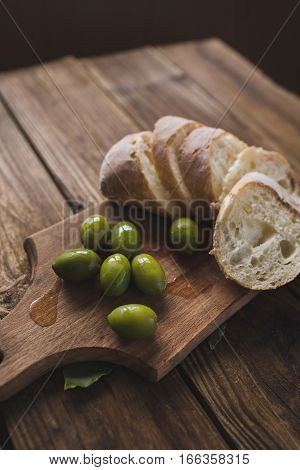 Green olives sliced ciabatta feta cheese on a wooden board. Spice. Garlic. Chees Feta. Ciabatta. Olives on a wooden background