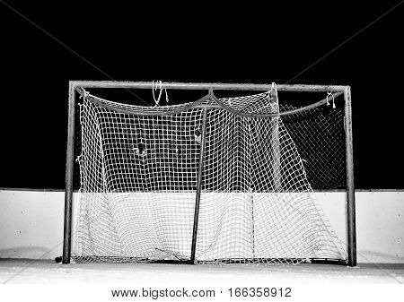 Close-up of tattered and frayed mesh on a hockey net on an outdoor ice skating rink at night in black and white
