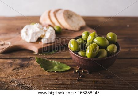 Green olives sliced ciabatta feta cheese on a wooden board. Spiced. Cheese Feta. Ciabatta. Olives on a light background