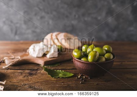 Green olives sliced ciabatta feta cheese on a wooden board. Spiced. Cheese Feta. Ciabatta. Olives on a gray abstract background