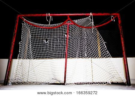 Close-up of tattered and frayed mesh on a hockey net on an outdoor ice skating rink at night