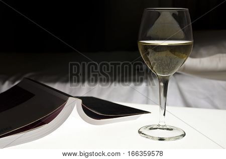 Book white wine next to a bed. Evening relax concept.