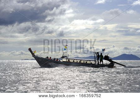 silhouette of anonymous long tail boat on sea horizon in Thailand at koh phi phi island in the province of krabi in travel destination and tourist vacation concept