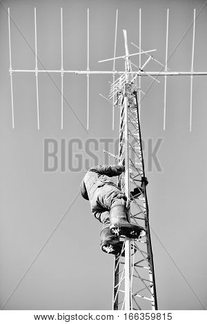 A man climbing up a steel communications tower for repairs in coveralls and rubber boots in black and white