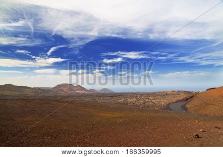 Montaineous desert landscape and cloudscape on a sunny day - Lanzarote Island