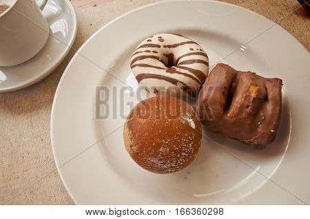 Sweet dessert - donuts and coffee. Pastry on a plate