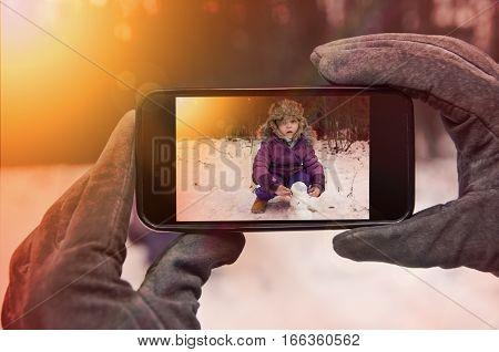 Woman taking picture of her baby playing in snow - winter pov shot.