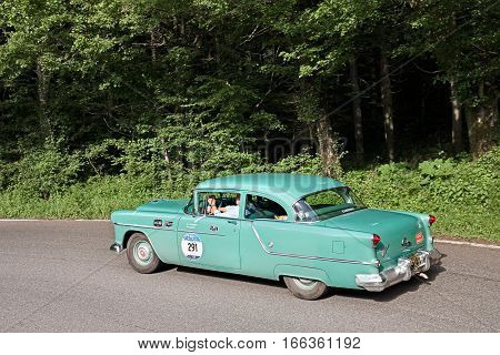 PASSO DELLA FUTA (FI) ITALY - MAY 21: driver and co-driver on a vintage American car Oldsmobile Super 88 (1954) in classic car race Mille Miglia on May 21, 2016 in Passo della Futa (FI) Italy