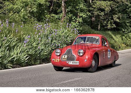 PASSO DELLA FUTA (FI) ITALY - MAY 21: driver and co-driver on a vintage sportscar Fiat 1100 [508 C] MM Berlinetta (1938) in classic car race Mille Miglia on May 21, 2016 in Passo della Futa (FI) Italy
