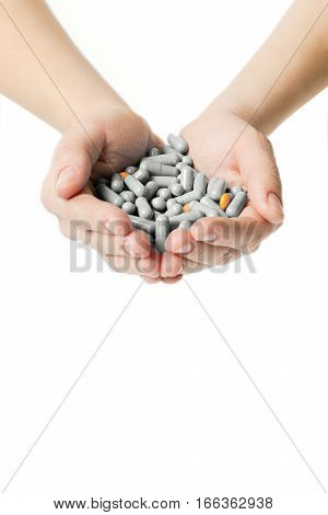 Hands Is Giving Gray Capsules And Orange Pills On White Background.
