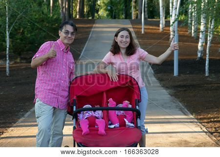 Happy parents with baby buggy and twin daughters in it walking in park
