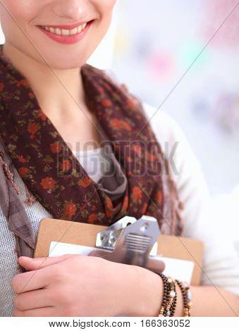 Portrait of attractive female fashion designer sitting at office desk.