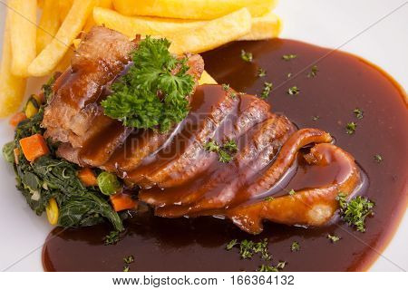 A nice dish of roasted duck breast confit in orange sauce served with fries on the table