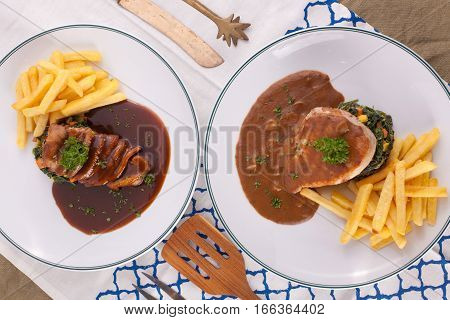 A nice dish of duck confit steak and pork steak served with fried potato, saute spinach and sauce on background with wooden utensils.