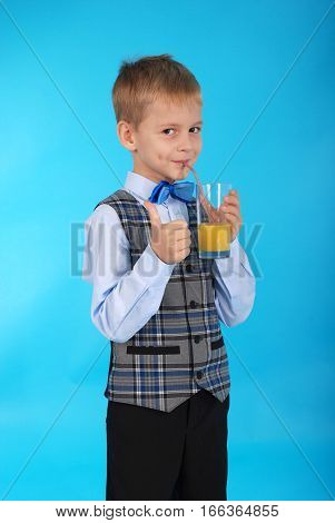 Boy in school uniform drinking orange juice and showing thumb up. Photos on a blue background