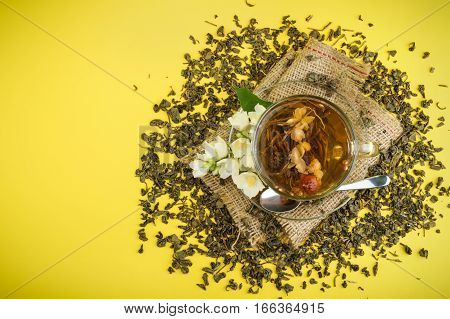 Cup of jasmine tea with flowers on yellow