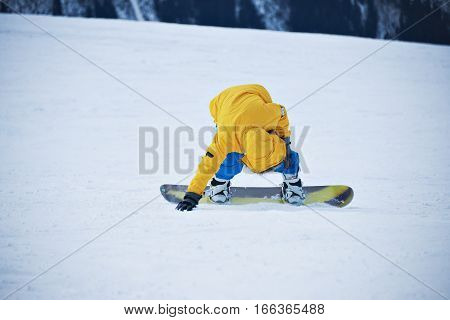 Snowboarder in yellow parka and blue pants stands up on slope after falling