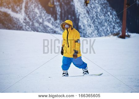 Snowboarder in bright yellow anorak and blue pants is ready to ride down the slope, looking at camera at sunny winer day in mountain ski resort