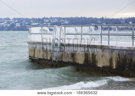 Pier covered with icicles after a winter storm on Lake Geneva.