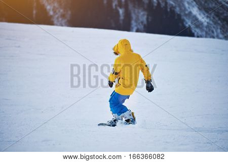 Back view of snowboarder in bright yellow jacket and blue pants rides down on snow slope at sunny winer day in mountain ski resort