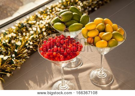 Fresh fruits perfect source of vitamins. Pomegranate feijoa red berry and kumquat healthy food for all seasons of the year.