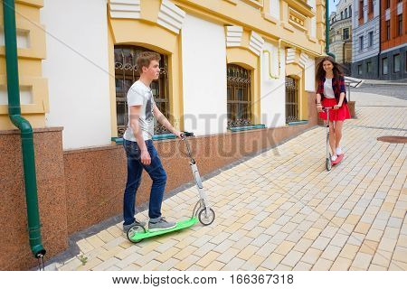 Brother And Sister Travel On Scooters