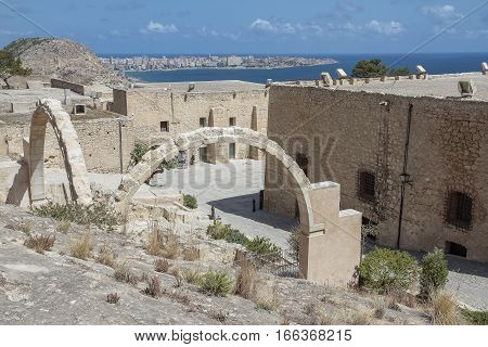 buildings of Santa Barbara castle Alicante spain with ruins of Santa Barbara hermitage on foreground and the mediterranean sea in the background