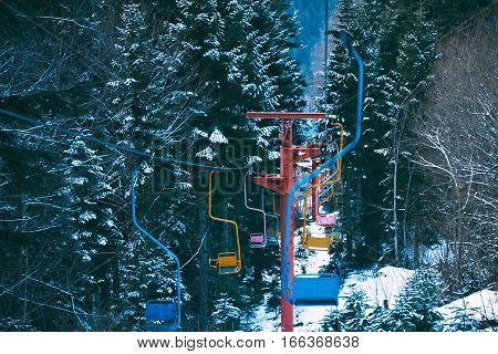 Top view shot of many pastel colored empty chairs of retro grunge ski lift, moving through winter pine forest covered in fresh snow in mountains