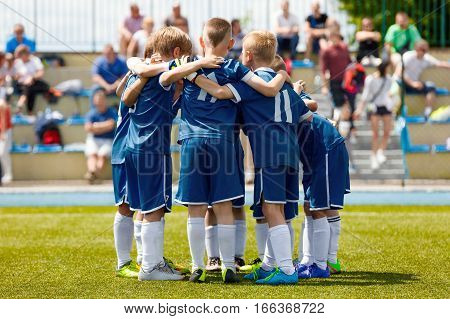 Children's Football Team on the Pitch. Boys in Blue Soccer Kits Standing Together on the Football Field. Motivated Young Soccer Players Before the Final Game of School Tournament