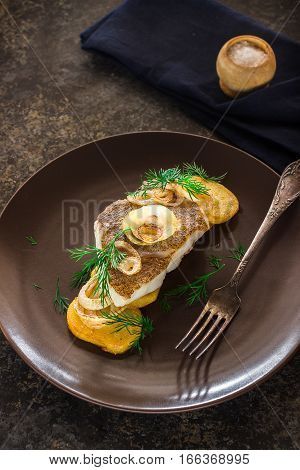 Fried Fish With Potato And Onion On Brown Plate.