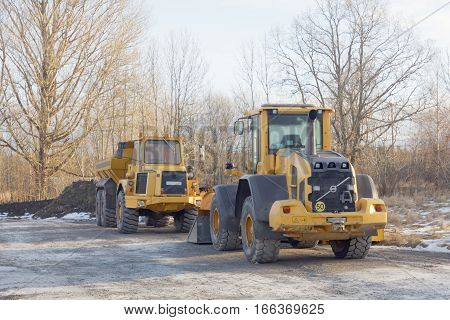 Parked yellow excavator and dumper truck beside each other