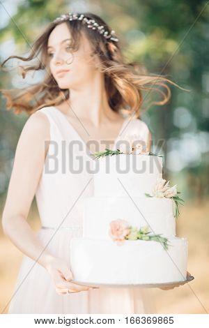 bride holding a wedding cake. fine art wedding photography