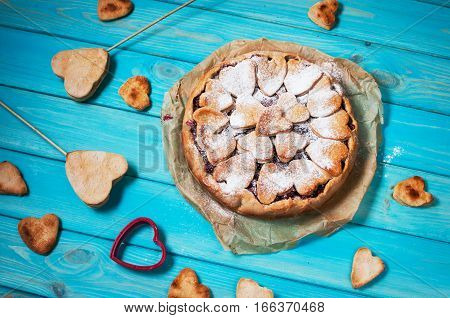 Idea for the celebration of Valentine's Day: cherry pie with the decor of the dough in the shape of heart on wooden table.