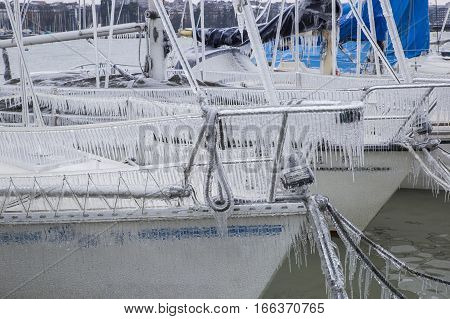 Sailboats covered with ice following a winter storm on Lake Geneva Switzerland.