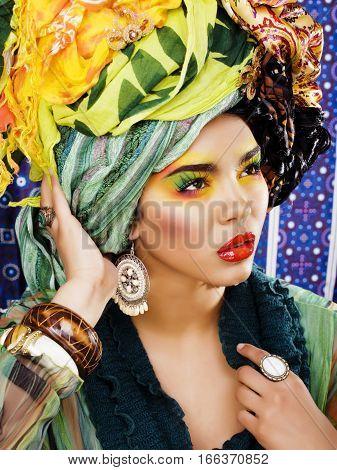 beauty bright woman with creative bright make up, many shawls on head, ethno look closeup