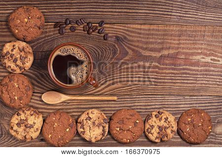 Cup of hot coffee and chocolate cookies on old wooden table top view. Space for text