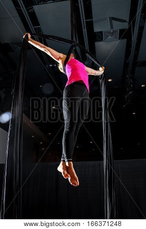 A female aerialist holds an teardrop iron cross pose from a belay loop on black silks with a black background and some lens flare for extra drama.