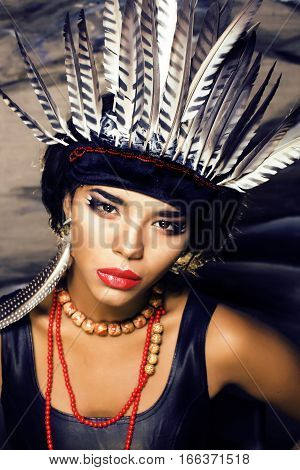 young pretty woman with make up like indian, feather in hair, fashion hallowen concept creative