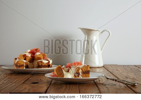 Piece of cake on small ceramic saucer next to silver dessert fork in front of unfocused cake and milk pot on rustic wooden table, isolated on white