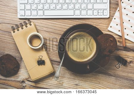 Vintage style hipster workplace, pc keyboard and coffee cup on wooden tabletop